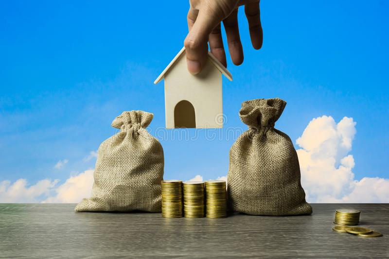Saving money, home loan, mortgage, a property investment for future concept. A man hand holding a small house model over stack of royalty free stock photos