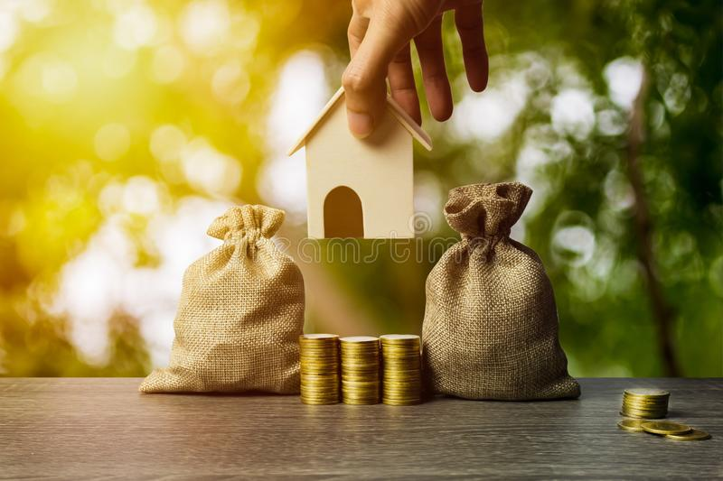 Saving money, home loan, mortgage, a property investment for future concept. A man hand holding a small house model over stack of. Coins and money bag on table stock photos