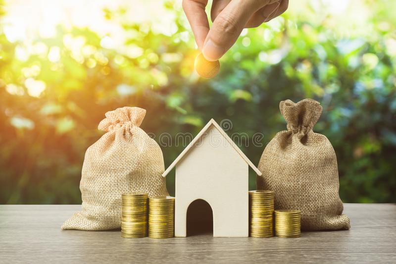 Saving money, home loan, mortgage, a property investment for future concept. A man hand putting money coin over small residence stock photography