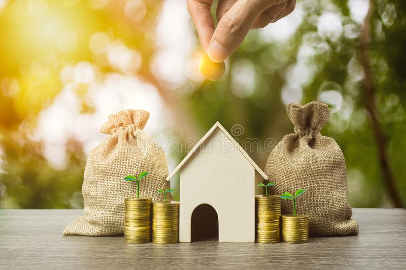 Saving money, home loan, mortgage, a property investment for future concept. A man hand putting money coin over small residence royalty free stock image