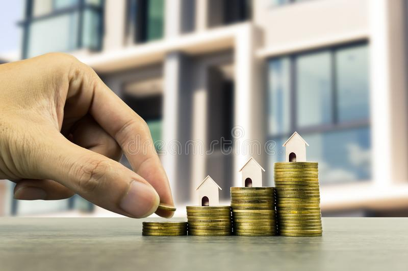 Saving money, home loan, mortgage, a property investment for future concept. A man hand putting money coin over small residence royalty free stock images
