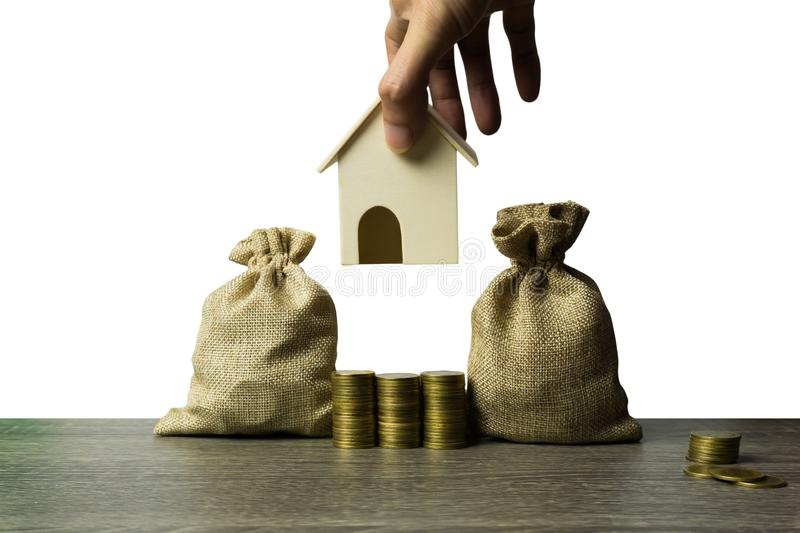 Saving money, home loan, mortgage, a property investment for future concept. A man hand a small residence house over stack of stock photography