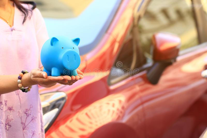 Saving money and loans for car concept, Young woman holding blue piggy with standing at the car parking lot background, Auto. Business royalty free stock photos