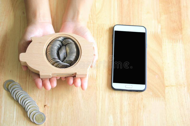 Saving money for prepare in future and investment concept, Woman hands holding piggy bank wood and a smartphone on the table. Background stock photos
