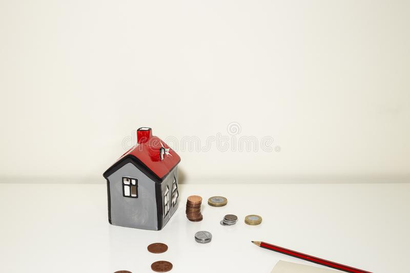 Mini house model coins. Saving money for property concept. Red roof House model, coins, pencil note book. Copy space stock photo