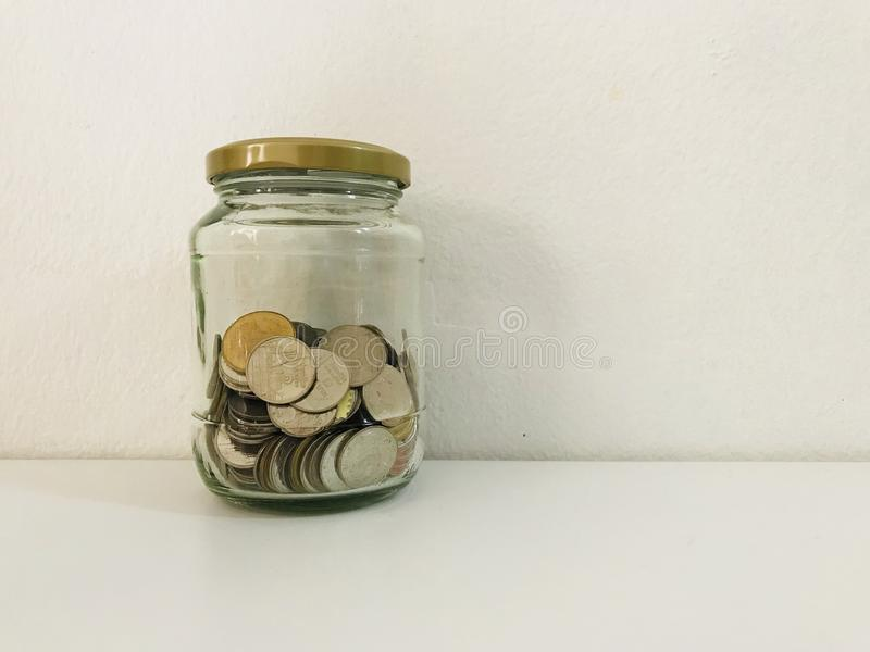 Saving money. Thai coin saving money in bottle glass stock photography