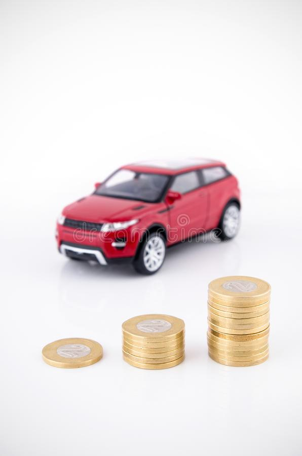 Saving money to buy a vehicle. Coins and car toy on white royalty free stock image
