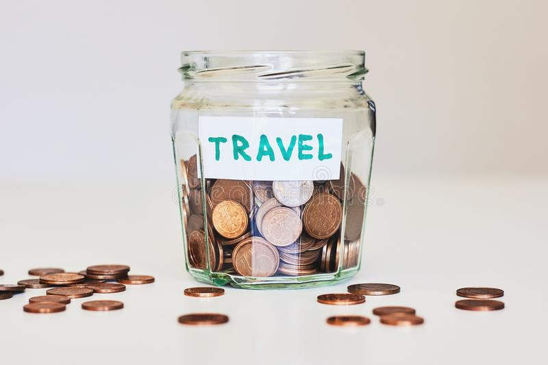 Saving money for travel concept. Glass jar full of coins and sign travel stock images