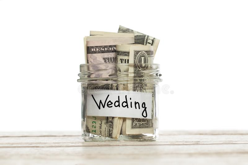 Saving money for wedding. Glass jar with us dollars on wooden table isolated stock image