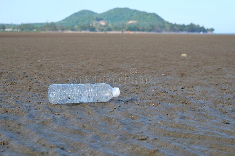 A plastic bottle of drinking water littering on the mud beach with a mountain background stock photo
