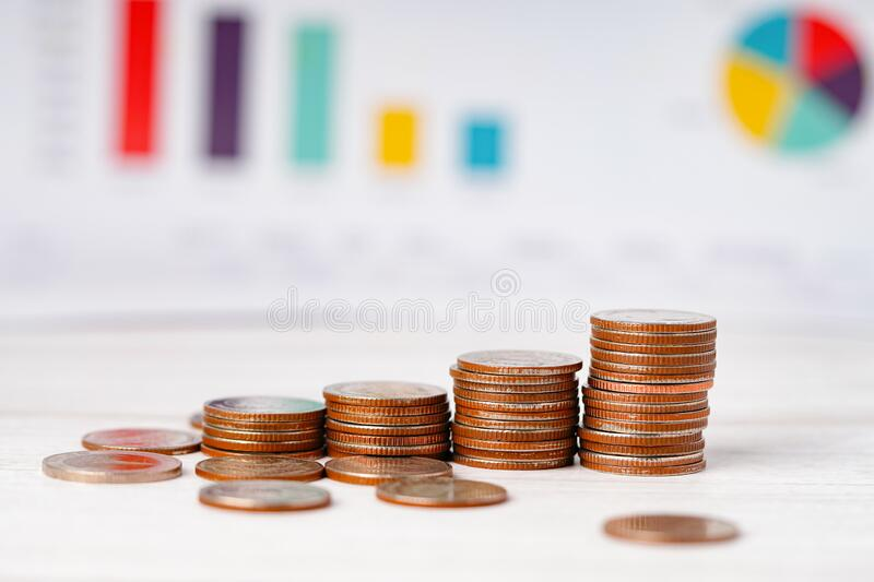 Saving stack coins money Charts and Graphs spreadsheet paper. royalty free stock photos