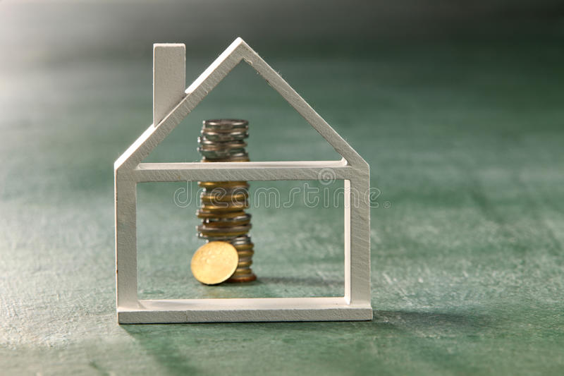 Saving to buy house. Model house and coins on the green background royalty free stock photos