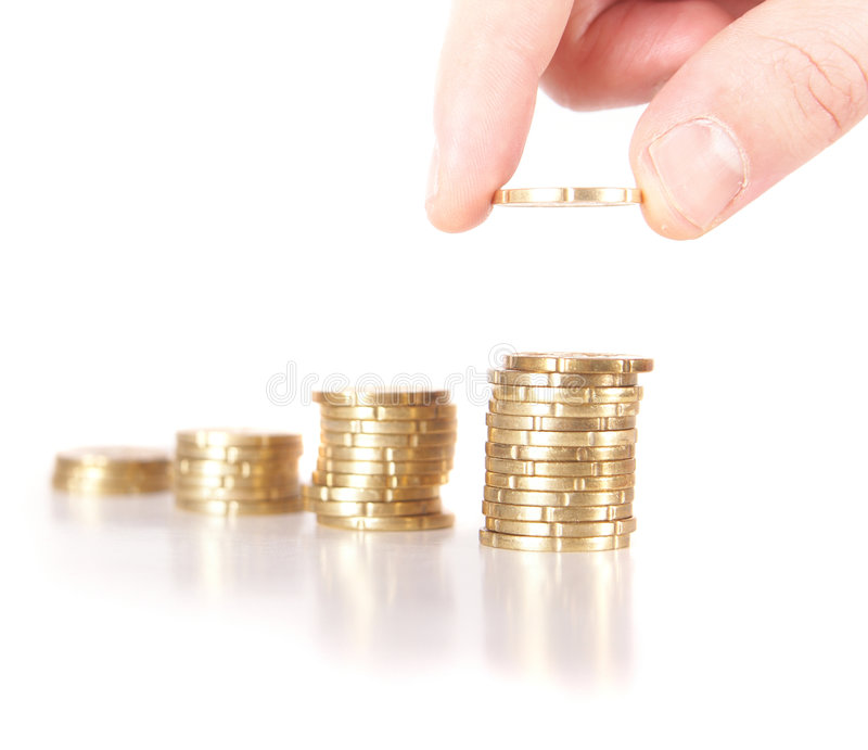 Savings. A hand is stacking up coins. The last coin is dropped. The coins are mirrored. Isolated over white. Ideal Businesshot stock photo