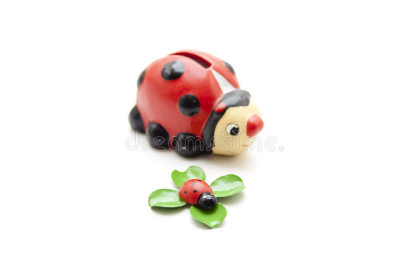 Savings can and ladybug on cloverleaf. And on white background stock images