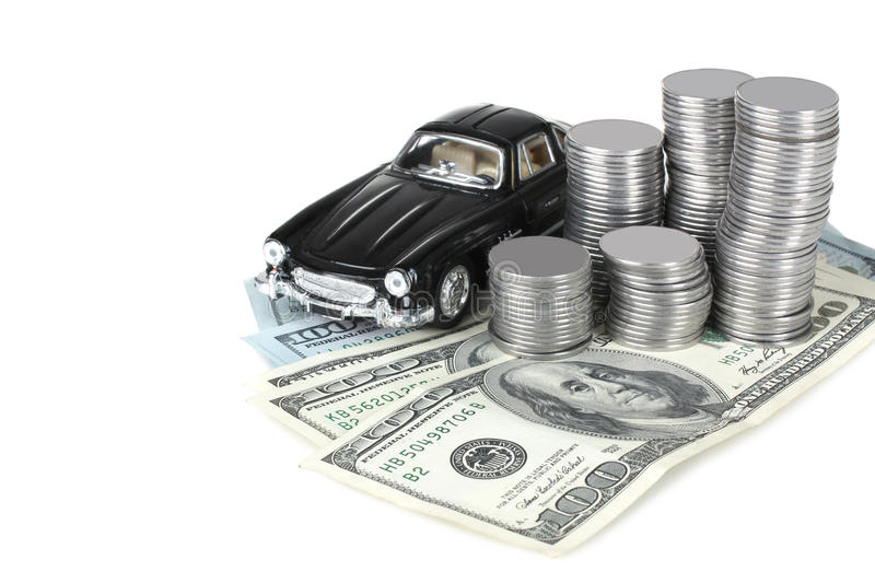 Savings on car. Beautiful toy car is near on the banknotes and pile of silver coins stacked in columns , isolated on white background royalty free stock images