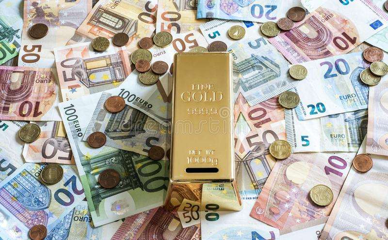 Savings Cash money concept euro banknotes all sizes and cent coins on desk piggy bank gold bar shape save. Savings Cash money concept euro banknotes of all sizes royalty free stock photo
