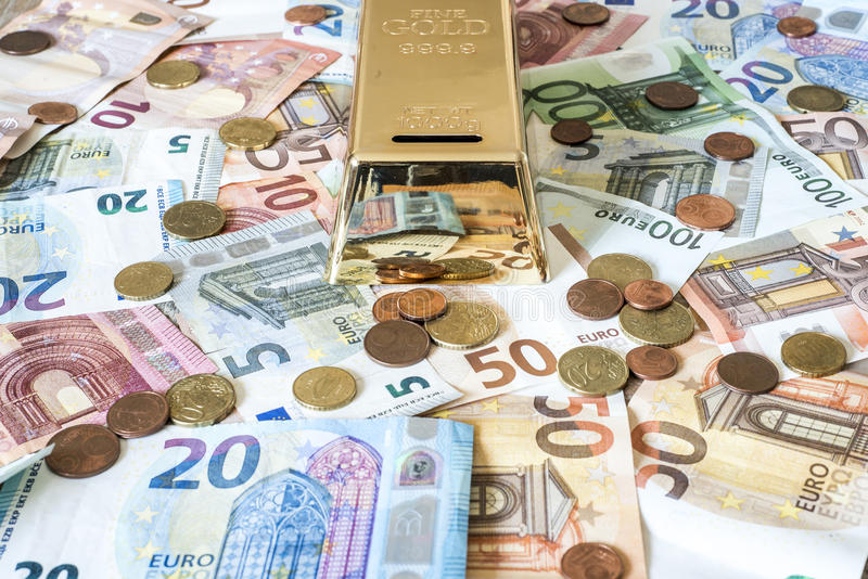 Savings Cash money concept euro banknotes all sizes and cent coins on desk piggy bank gold bar shape save. Savings Cash money concept euro banknotes of all sizes royalty free stock image