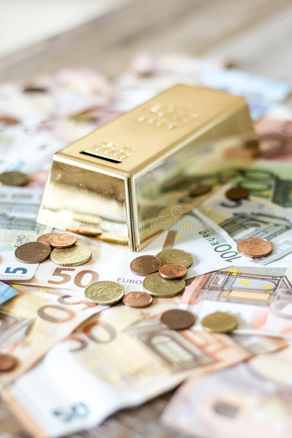 Savings Cash money concept euro banknotes all sizes and cent coins on desk piggy bank gold bar shape save. Savings Cash money concept euro banknotes of all sizes stock image