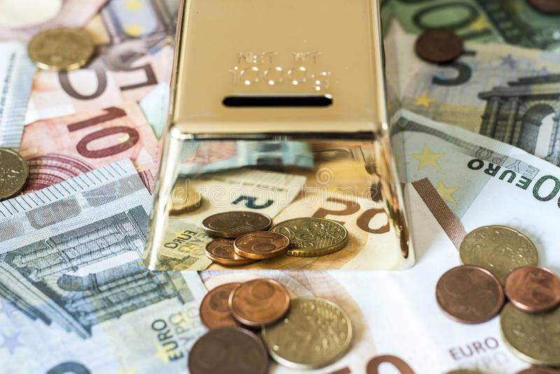 Savings Cash money concept euro banknotes all sizes and cent coins on desk piggy bank gold bar shape save. Savings Cash money concept euro banknotes of all sizes royalty free stock photos