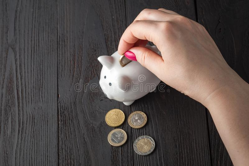 Savings concept,white piggy bank with human female hand inserting  coin inside stock photos