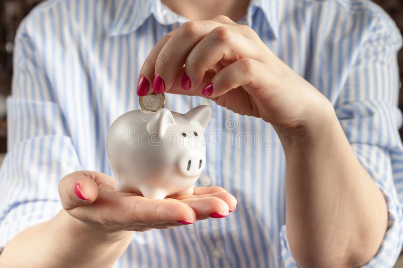 Savings concept,white piggy bank with human female hand inserting  coin inside royalty free stock photography