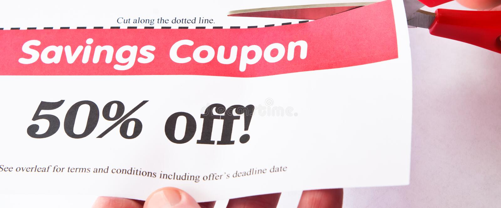 Savings Coupon. Scissors cutting dotted line of a 50% off savings coupon. Hands visible stock photo