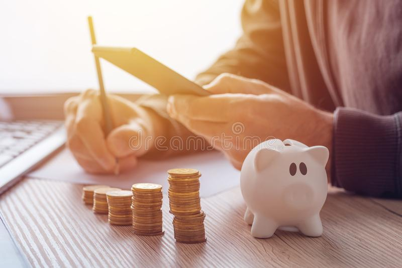 Savings, finances, economy and home budget. Calculations. Close up of man doing calculations and writing notes at home royalty free stock photo