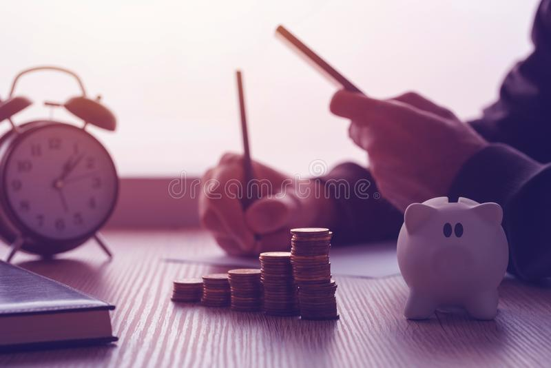 Savings, finances, economy and home budget. Calculations. Close up of man doing calculations and writing notes at home royalty free stock images