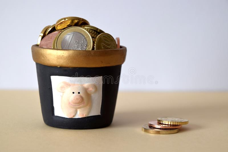 Savings concept, diverse euro coins in piggy-bank jar royalty free stock image