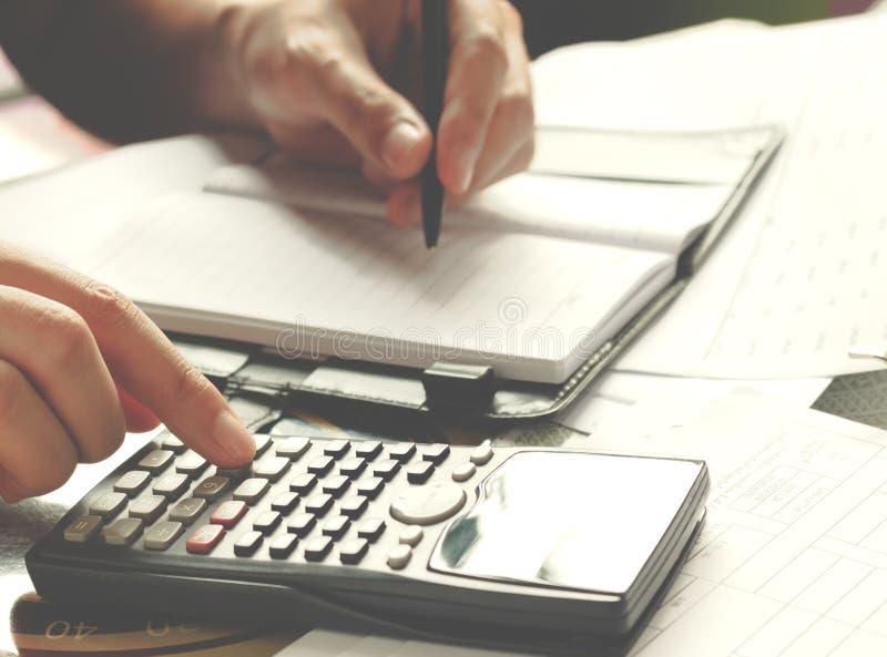 Savings, finanse, gospodarka i domowy pojęcie, - zakończenie up mężczyzna z kalkulatora liczeniem robi notatkom w domu obraz royalty free