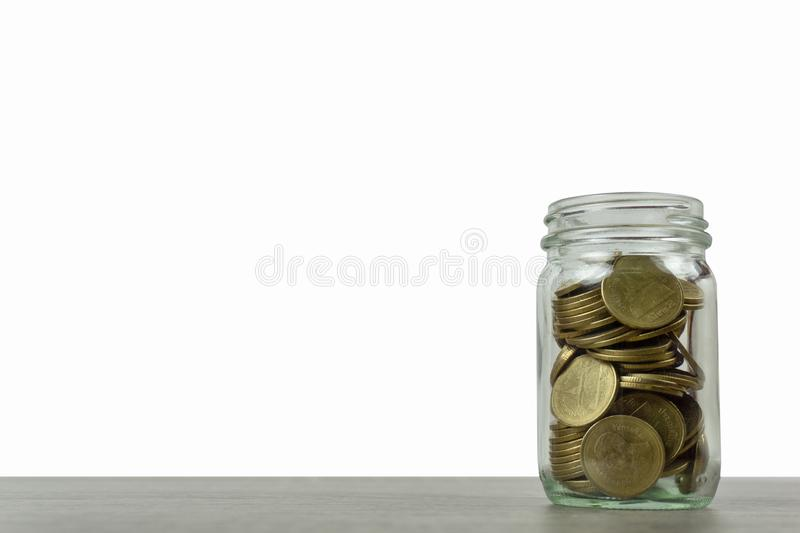Savings and investment concepts. Stack of coins in a glass jar on wooden table isolated on white background and space.  royalty free stock image