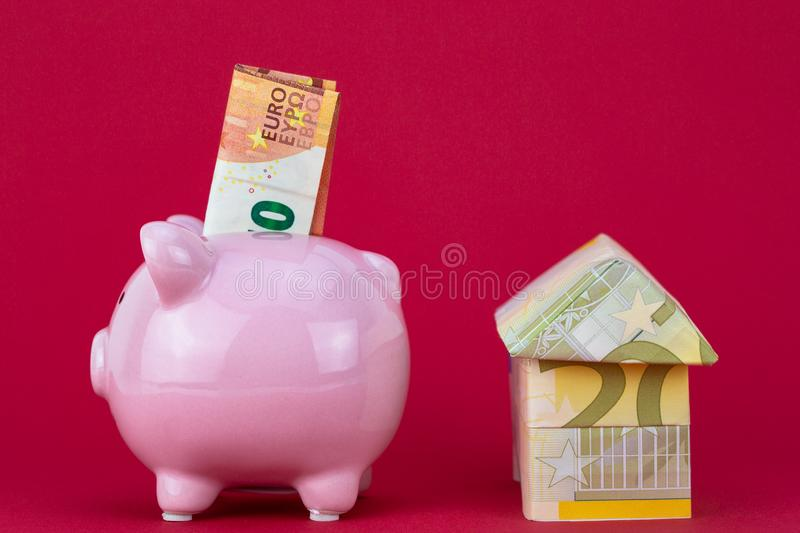 Savings and investment - Piggy bank, money house on raspberry color background. Closeup on Savings and investment - Piggy bank, money house on raspberry color royalty free stock images