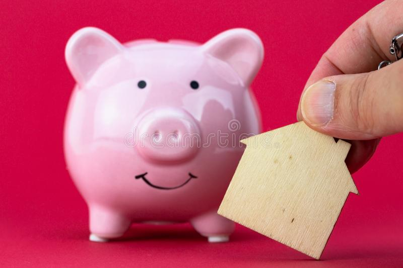 Savings and investment - Piggy bank, wood house on raspberry color background. Closeup on Savings and investment - Piggy bank, wood house on raspberry color stock image
