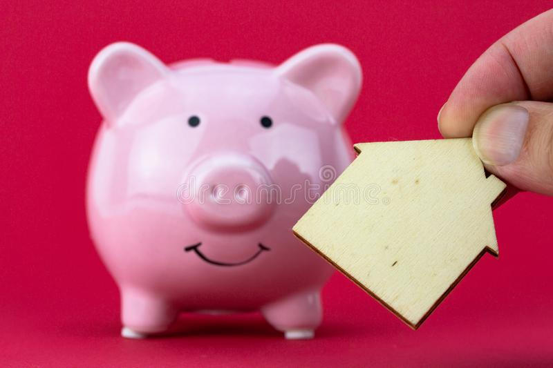 Savings and investment - Piggy bank, wood house on raspberry color background. Closeup on Savings and investment - Piggy bank, wood house on raspberry color royalty free stock photos