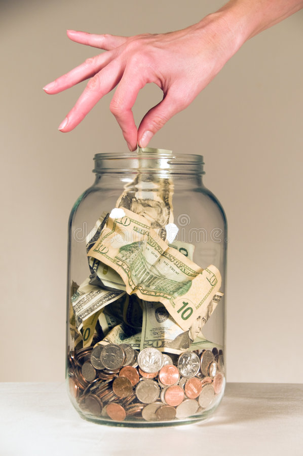 Savings Jar. Close up of a female hand picking a twenty dollar bill out of a clear glass savings or tips bottle stock photo