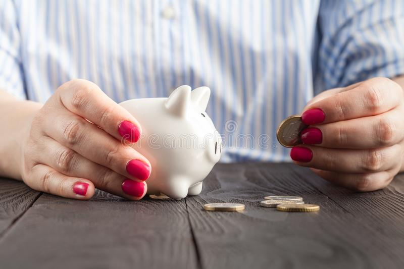 Savings, money, annuity insurance, retirement and people concept - close up of senior woman hand putting coin into piggy bank stock photography