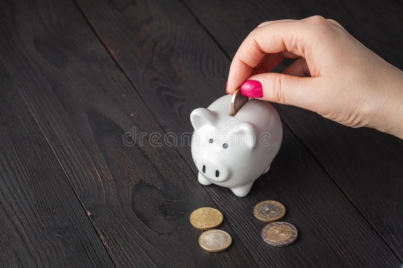 Savings, money, annuity insurance, retirement and people concept - close up of senior woman hand putting coin into piggy bank stock images