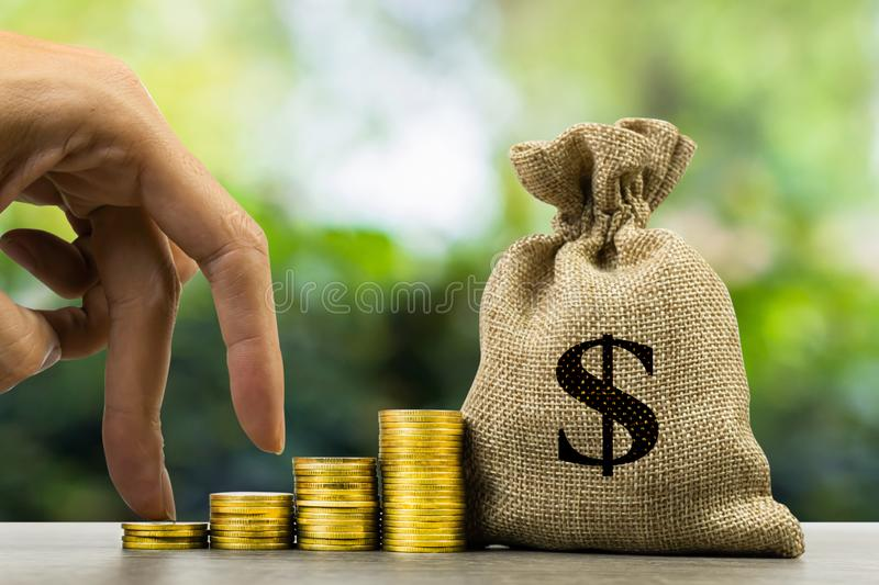 Savings money and investment, Making money concept. A finger hand walk up on growing stack of golden coins and money bag on woo. Table. Depicts long-term royalty free stock photo