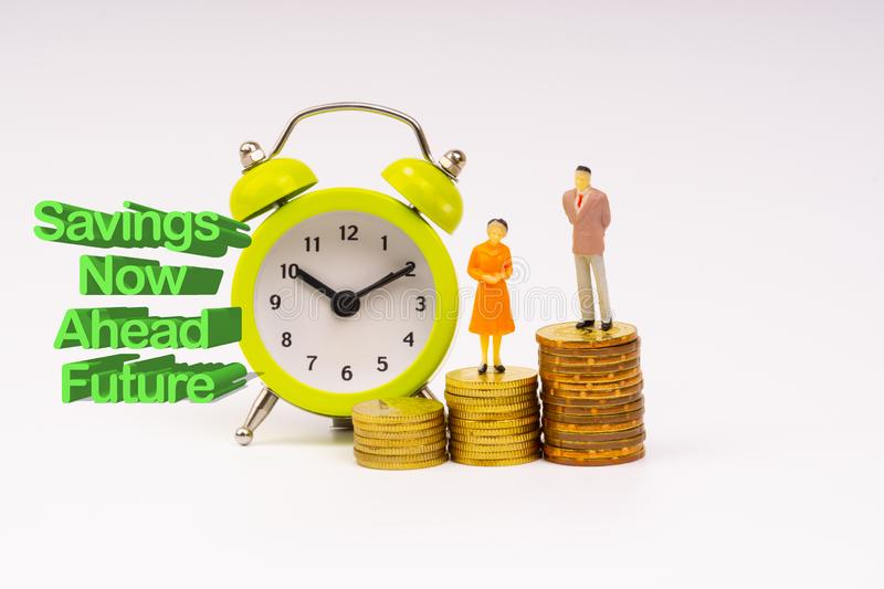 SAVINGS NOW AHEAD FUTURE inscription written, alarm clock, coins and businessman miniature stock photography