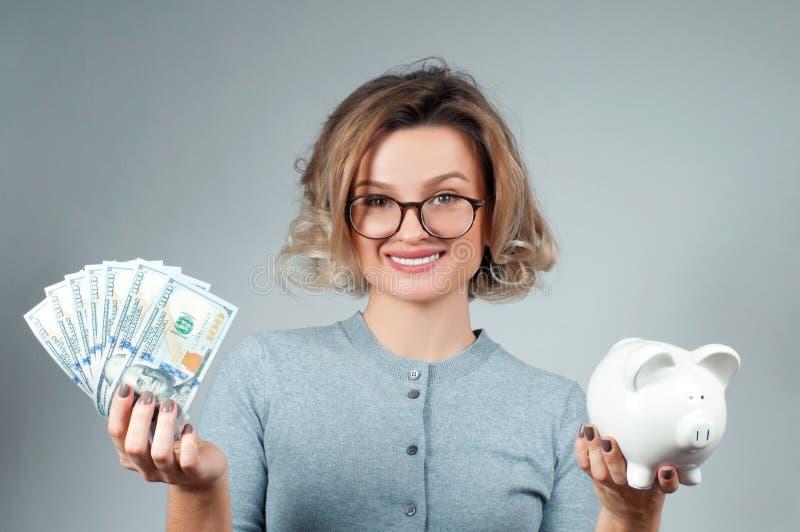 Savings pojęcie Kobiety mienia prosiątka bank i wiązka pieniędzy banknoty fotografia royalty free