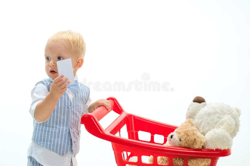 Savings on purchases. little boy child in toy shop with credit card. shopping for children. little boy go shopping with stock photo