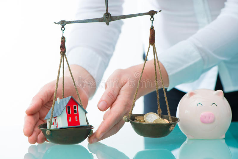 Savings or real estate investment concept. With house and cash money on scale stock images