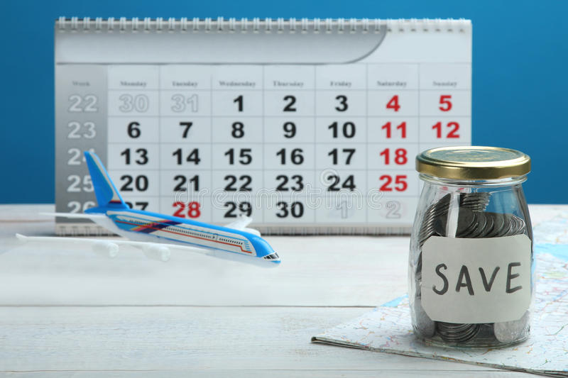 Savings on travel. Toy airplane, savings, calendar and map on a wooden table on a wooden background royalty free stock photography