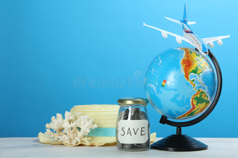 Savings on travel. Toy airplane, globe, savings and beach hat on a blue background royalty free stock photo