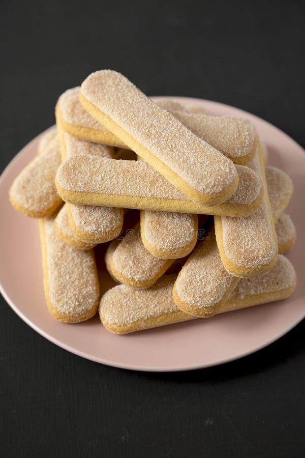 Savoiardi eller sockerkaksbit i form av ett fingerkakor på en rosa platta över svart bakgrund, sidosikt N?rbild arkivfoton