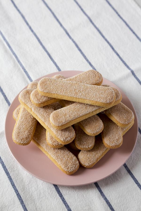 Savoiardi or ladyfingers cookies on pink plate, low angle view. Closeup. Copy space.  royalty free stock image