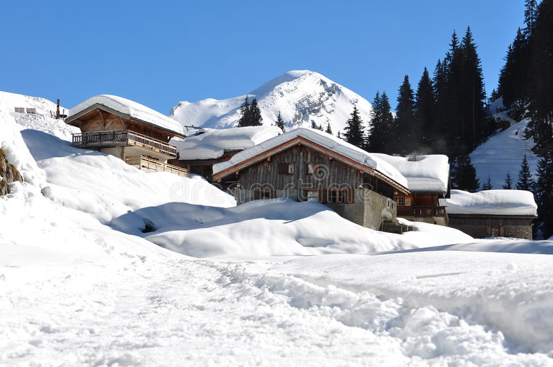 Savoie village in winter. Cottages of Savoie village in the mountains to the snowy roofs stock photo
