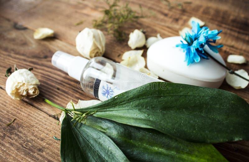 Savon et bodyspray avec des fleurs sur un fond en bois photographie stock libre de droits