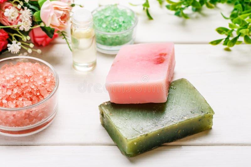 Savon fait main avec du sel de mer, le pétrole cosmétique et les fleurs roses sur une table en bois blanche images stock