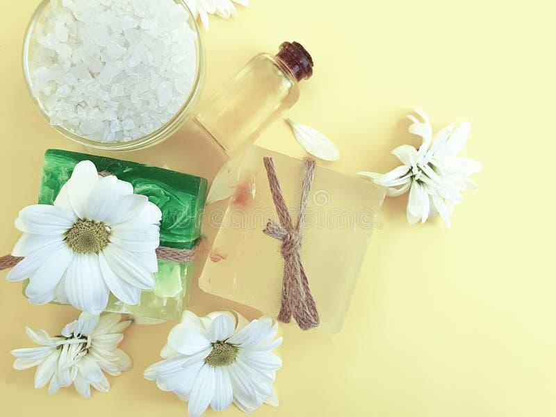 Savon, sel, huile, hygiène organique de fleur d'arome d'extrait de chrysanthème sur un fond jaune photo stock